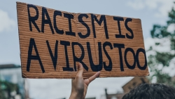 """A placard that says """"Racism is a virus too"""", held by a black hand with a tree at the back. Source: Unplash website (CC)"""